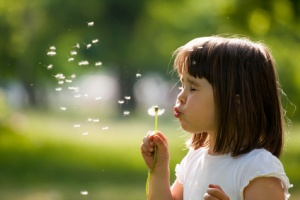 Beautiful child with dandelion flower in spring park. Happy kid having fun outdoors.